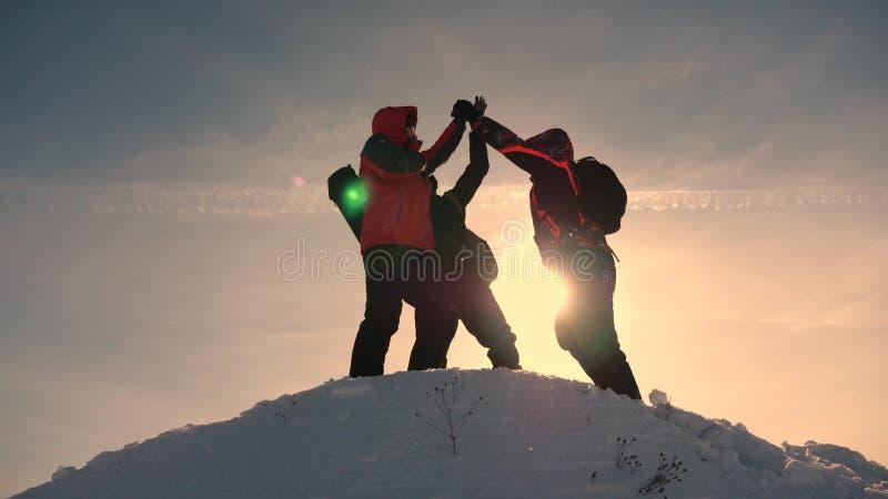 Εργασία και νίκη ομάδας Οι τουρίστες έρχονται να ολοκληρώσουν του χιονώδους λόφου και να χαρούν για τη νίκη ενάντια στο σκηνικό ε στοκ φωτογραφία με δικαίωμα ελεύθερης χρήσης