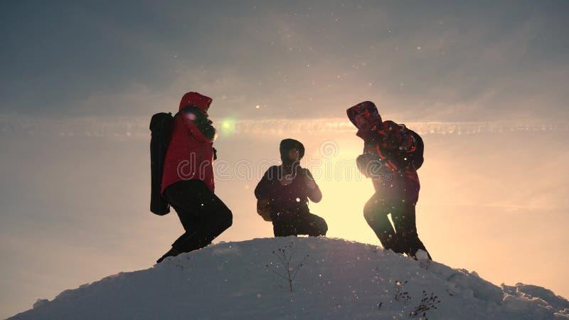 Εργασία και νίκη ομάδας Οι τουρίστες έρχονται να ολοκληρώσουν του χιονώδους λόφου και να χαρούν για τη νίκη ενάντια στο σκηνικό ε στοκ φωτογραφίες