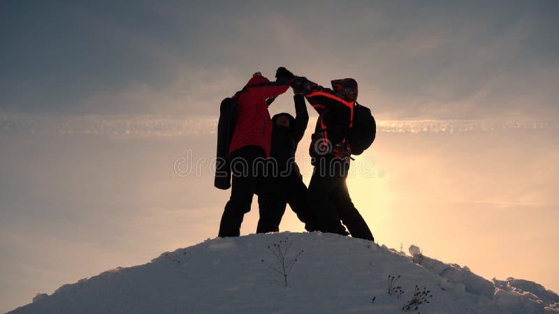 Εργασία και νίκη ομάδας Οι τουρίστες έρχονται να ολοκληρώσουν του χιονώδους λόφου και να χαρούν για τη νίκη ενάντια στο σκηνικό ε στοκ εικόνες
