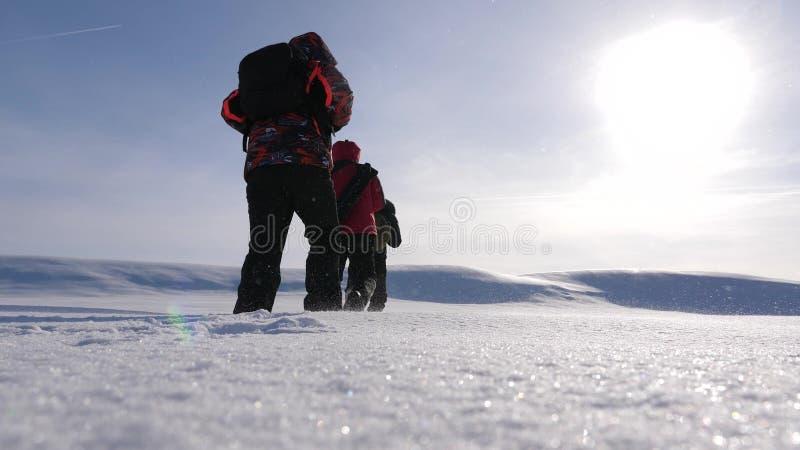 Εργασία και νίκη ομάδας τρεις τουρίστες αλπινιστών ακολουθούν ο ένας τον άλλον στη χιονώδη έρημο η ομάδα των επιχειρηματιών πηγαί στοκ εικόνες