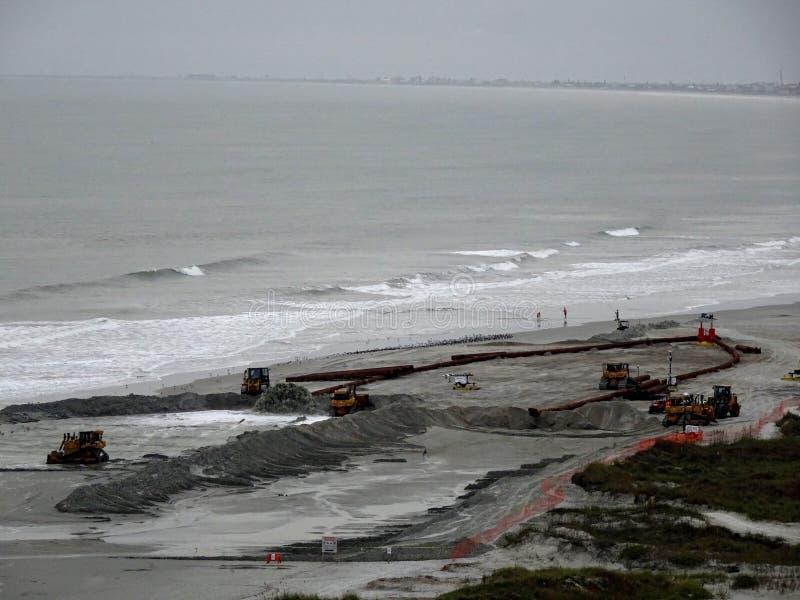 Εργασίες πληρώματος κατασκευής για να προετοιμάσει την παραλία μπροστά από τη θύελλα στοκ φωτογραφία