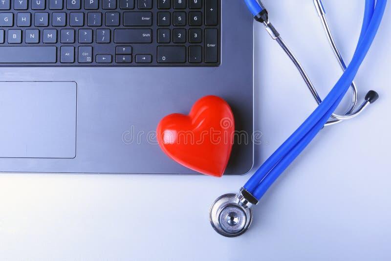 Εργασιακός χώρος του γιατρού με το στηθοσκόπιο, την κόκκινη καρδιά, το lap-top, rx τη συνταγή και το σημειωματάριο στον άσπρο πίν στοκ εικόνα