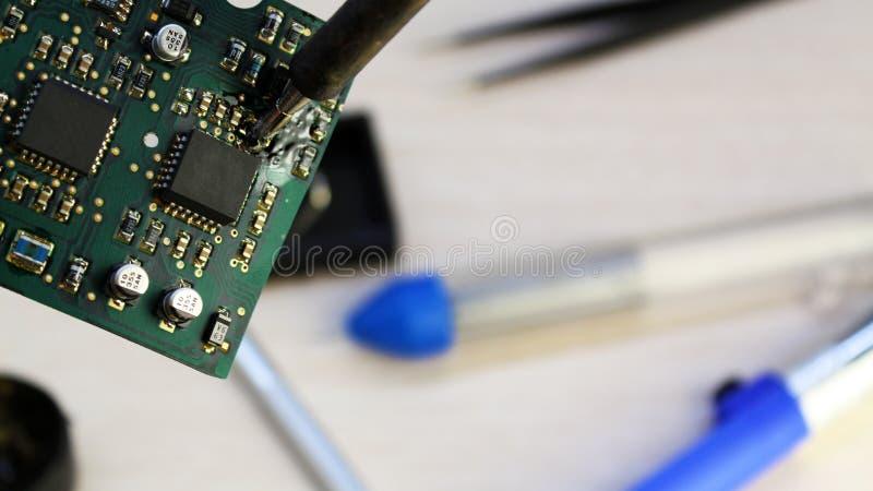 Εργαστήριο στην επισκευή των οικιακών συσκευών, της ηλεκτρονικής και των επεξεργαστών συγκολλώντας συγκολλώντας σίδηρος πινάκων,  στοκ εικόνες