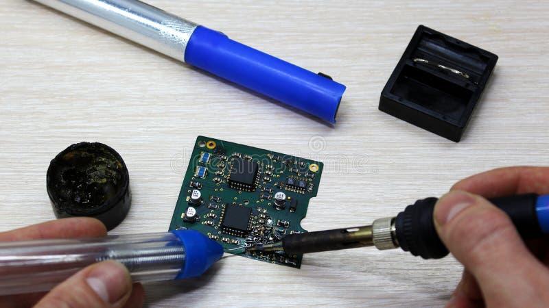 Εργαστήριο στην επισκευή των οικιακών συσκευών, της ηλεκτρονικής και των επεξεργαστών συγκολλώντας συγκολλώντας σίδηρος πινάκων,  στοκ εικόνα