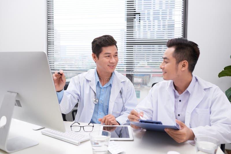 Εργατικοί γιατροί που αναθεωρούν το αρχείο του ασθενή στοκ φωτογραφία με δικαίωμα ελεύθερης χρήσης