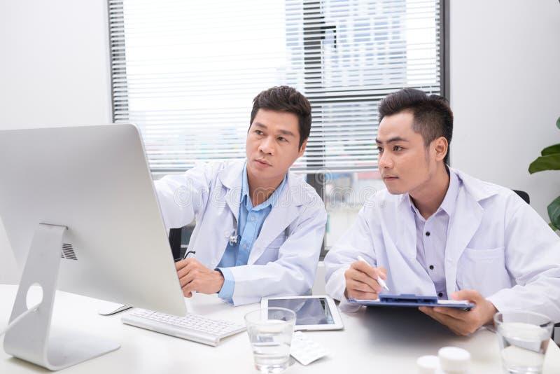 Εργατικοί γιατροί που αναθεωρούν το αρχείο του ασθενή στοκ φωτογραφίες με δικαίωμα ελεύθερης χρήσης