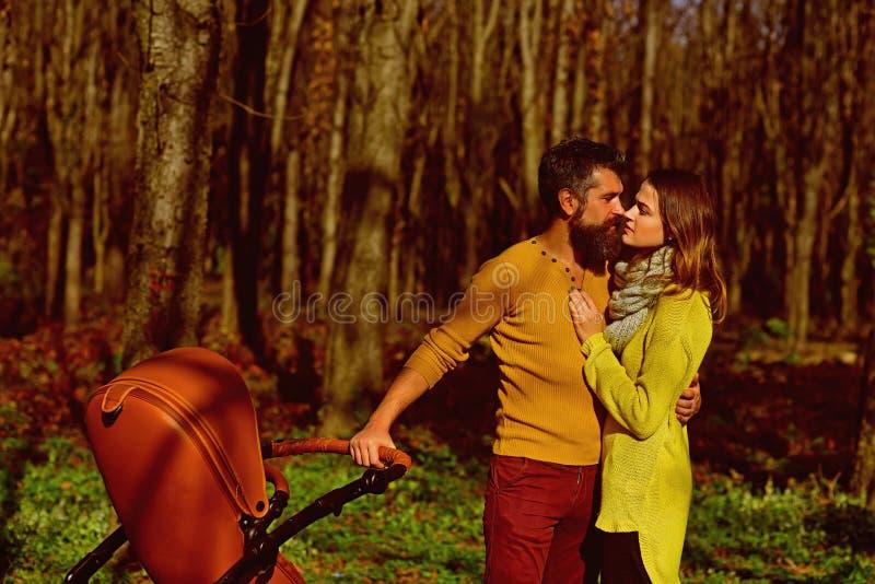 Ερωτευμένο φιλί ζεύγους στο πάρκο ευχαρίστησης Η ευτυχής οικογένεια με το καροτσάκι μωρών ξοδεύει το χρόνο με την ευχαρίστηση από στοκ φωτογραφίες με δικαίωμα ελεύθερης χρήσης