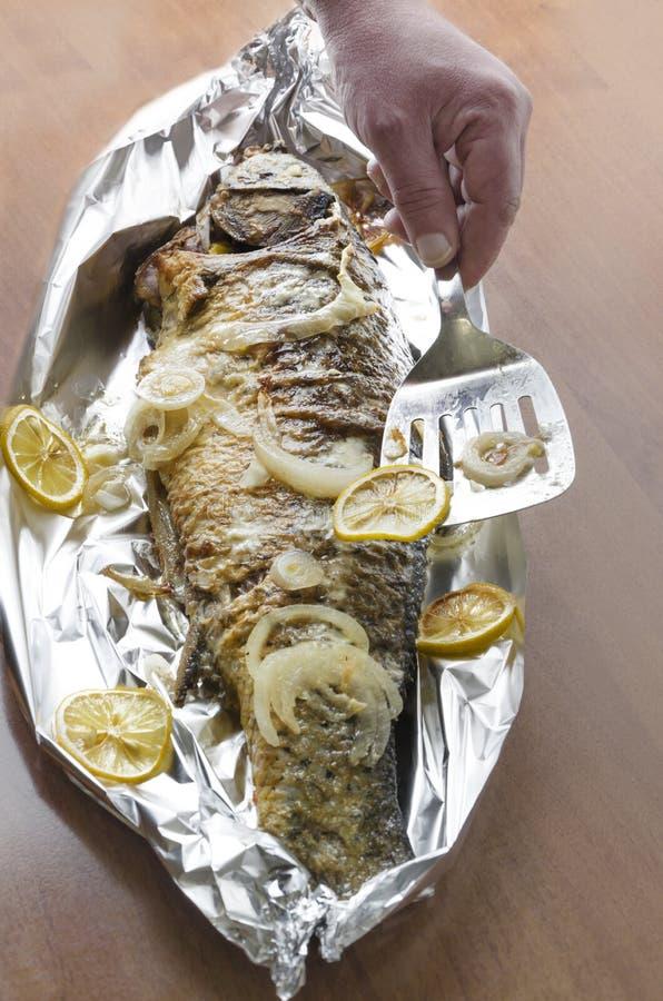 Εύγευστα φρέσκα ψημένα στη σχάρα ψάρια κυπρίνων με τις φέτες του λεμονιού Αρχιμάγειρας που χρησιμοποιεί spatula για να βάλει τη φ στοκ φωτογραφίες με δικαίωμα ελεύθερης χρήσης