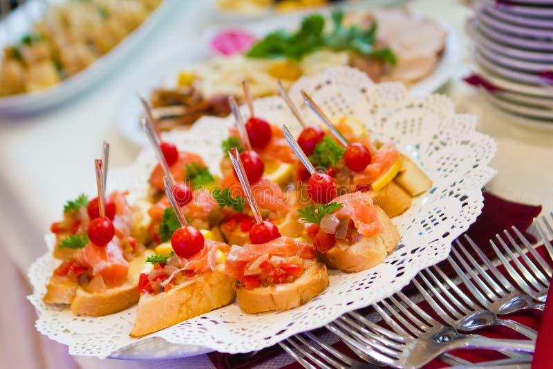 Εύγευστα πιάτα πρόχειρων φαγητών στον πίνακα μπουφέδων στο συμπόσιο κομμάτων, που εξυπηρετεί την υπηρεσία στο υπαίθριο κόμμα στοκ εικόνες