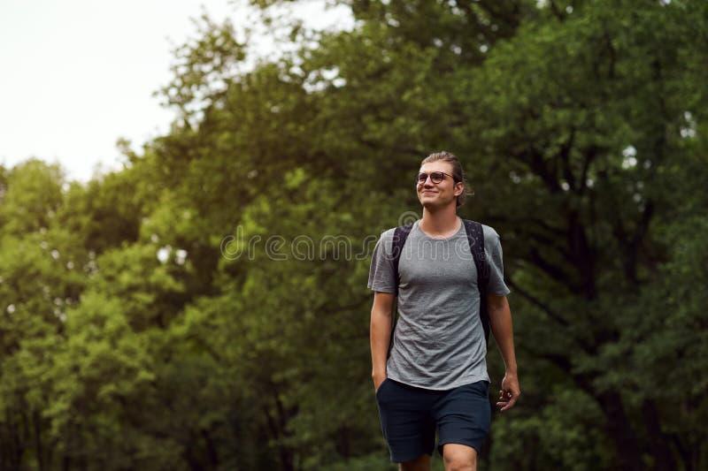 Εύθυμος ελκυστικός νέος σπουδαστής με το bagpack, που χαμογελά και που περνά καλά περπατώντας δημόσια το πάρκο Όμορφη ηλιόλουστη  στοκ φωτογραφία με δικαίωμα ελεύθερης χρήσης