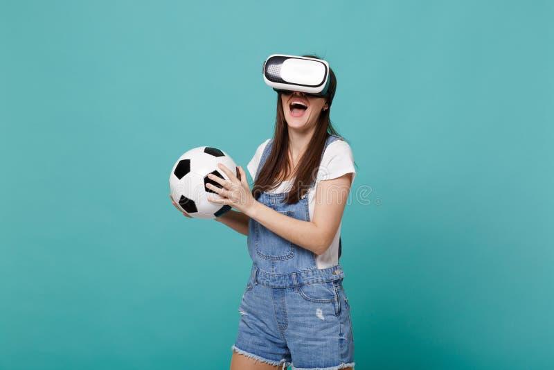 Εύθυμος οπαδός ποδοσφαίρου νέων κοριτσιών που κοιτάζει στο παιχνίδι σφαιρών ποδοσφαίρου εκμετάλλευσης κασκών που απομονώνεται στο στοκ εικόνα με δικαίωμα ελεύθερης χρήσης