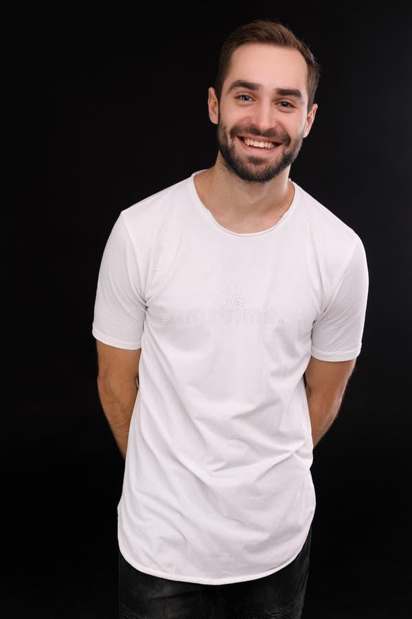 Εύθυμος τύπος σε μια άσπρη μπλούζα σε ένα μαύρο υπόβαθρο στοκ εικόνα