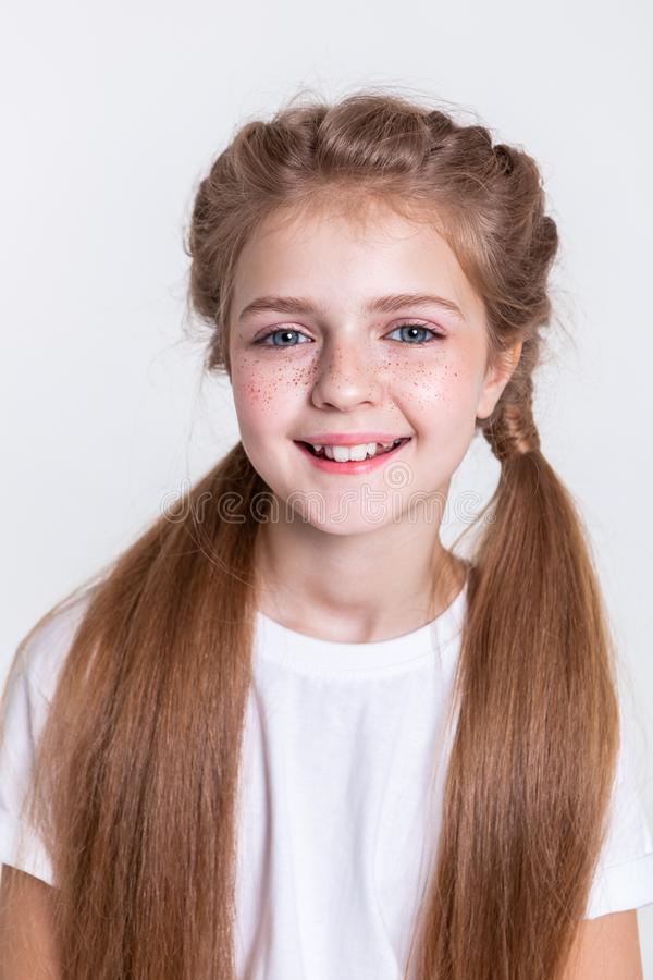 Εύθυμο θετικό όμορφο παιδί που είναι στη μεγάλη διάθεση και που παρουσιάζει χαμόγελό της στοκ φωτογραφία με δικαίωμα ελεύθερης χρήσης