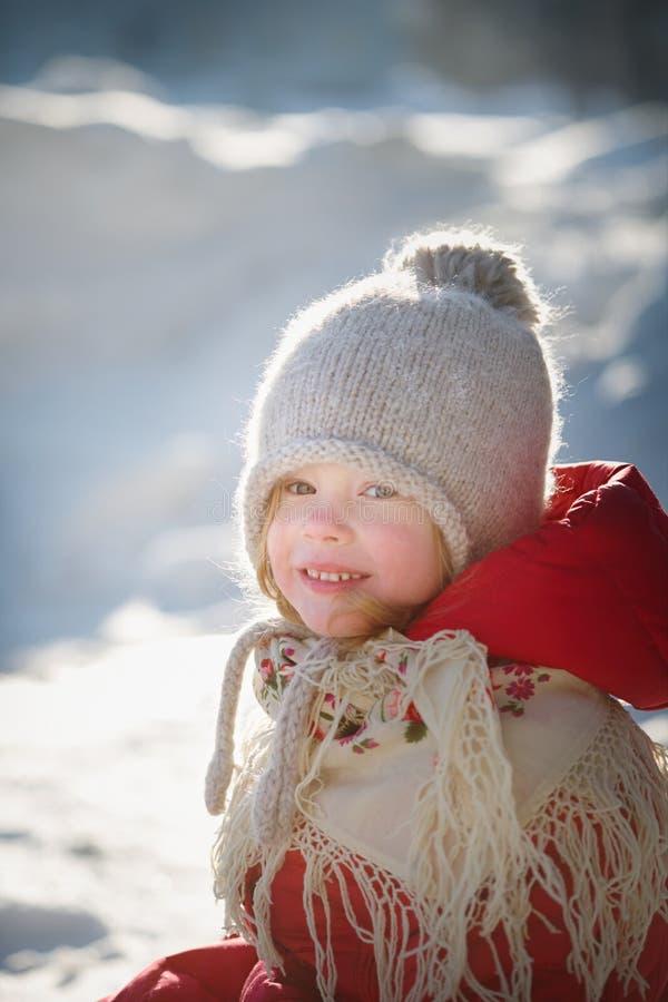 Εύθυμο μικρό κορίτσι σε ένα πλεκτό καπέλο, ένα κόκκινο παλτό και ένα όμορφο σάλι στοκ εικόνα με δικαίωμα ελεύθερης χρήσης