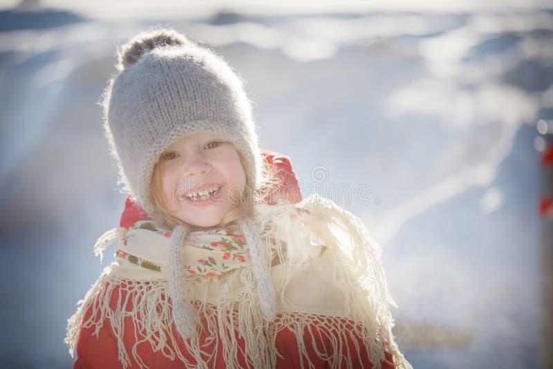 Εύθυμο μικρό κορίτσι σε ένα πλεκτό καπέλο, ένα κόκκινο παλτό και ένα όμορφο σάλι στοκ εικόνες