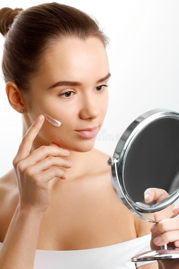 'Εφαρμογή' του διαφανούς βερνικιού δερμάτων προσοχής Όμορφη γυναίκα που βάζει την κρέμα προσώπου Εφαρμόζει moisturizer την κρέμα  στοκ εικόνα
