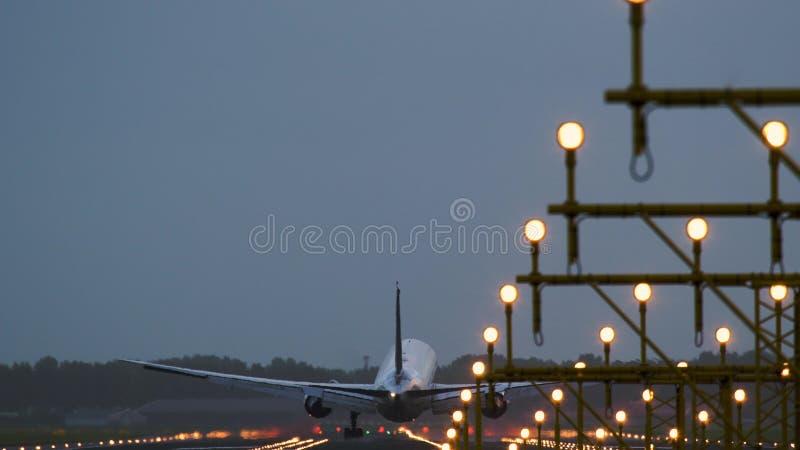 Ευρέα εδάφη αεροπλάνων σωμάτων στο φωτισμένο διάδρομο στοκ φωτογραφία με δικαίωμα ελεύθερης χρήσης