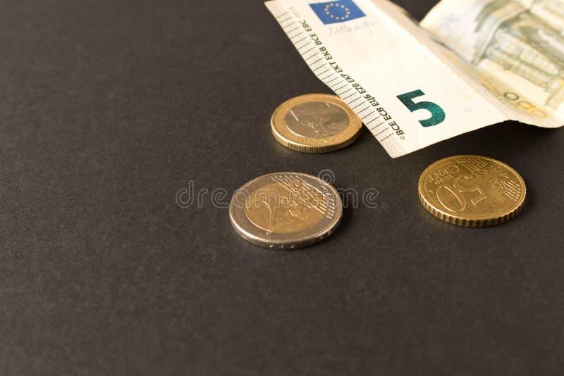 5 ευρο- τραπεζογραμμάτια και νομίσματα στο σκοτεινό υπόβαθρο κλείστε επάνω Η έννοια της αποταμίευσης στοκ εικόνα με δικαίωμα ελεύθερης χρήσης