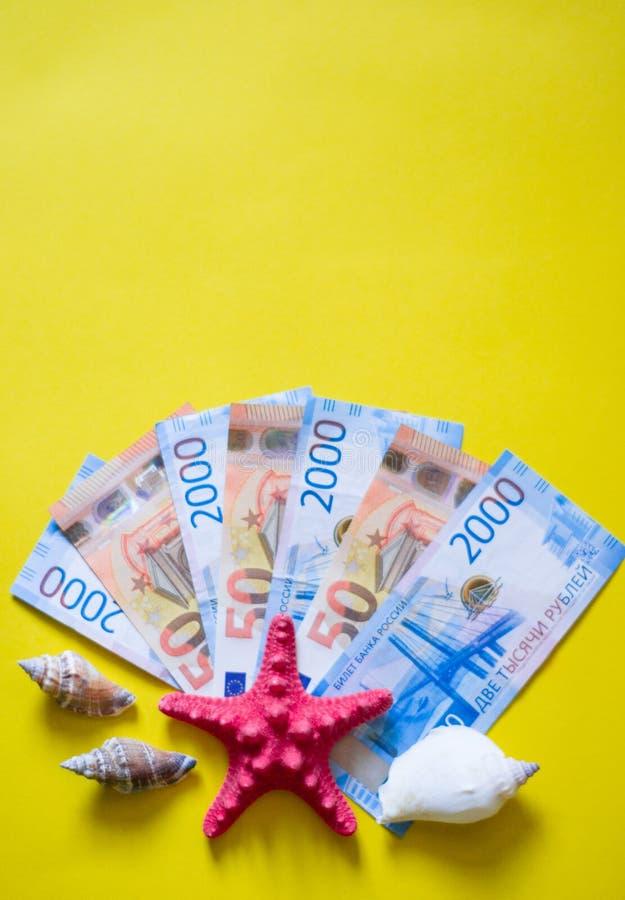 Ευρώ και ρούβλι με τα κόκκινα και άσπρα θαλασσινά κοχύλια στο κίτρινο backgrong στοκ εικόνες με δικαίωμα ελεύθερης χρήσης
