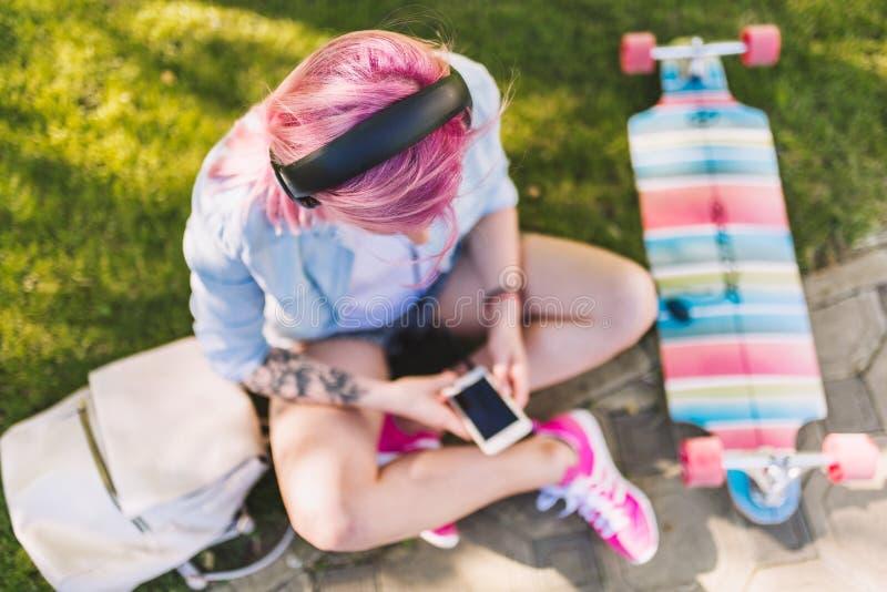 Ευρωπαία όμορφη γυναίκα με τη ρόδινη τρίχα στα ακουστικά που ακούει τη μουσική από τη συνεδρίαση smartphone στο πάρκο στην πράσιν στοκ εικόνες