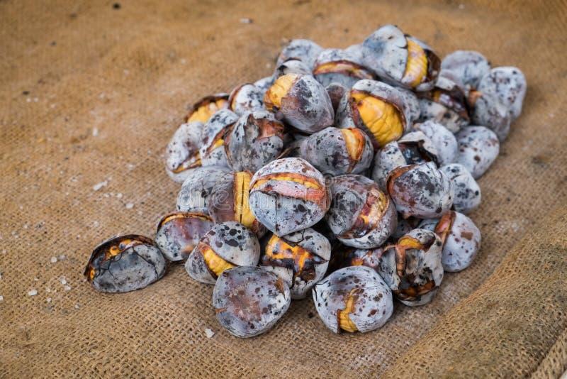 Ευρωπαϊκά ψημένα λιχουδιά κάστανα που πωλούνται στις οδούς σε ένα burlap υπόβαθρο στοκ εικόνα με δικαίωμα ελεύθερης χρήσης