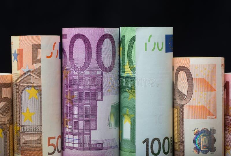 Ευρωπαϊκά χρήματα εγγράφου στους ρόλους στο μαύρο υπόβαθρο στοκ εικόνες