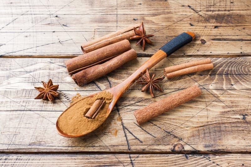 Ευώδη ραβδιά κανέλας καρυκευμάτων και έδαφος, γλυκάνισο αστεριών στο ξύλινο υπόβαθρο στοκ εικόνες