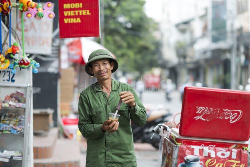 Ευτυχές άτομο που πίνει έναν παγωμένο καφέ πράσινο σε ομοιόμορφο στο Ανόι, Βιετνάμ Βιετναμέζικο χαμογελώντας άτομο με μια ανανέωσ στοκ εικόνα με δικαίωμα ελεύθερης χρήσης