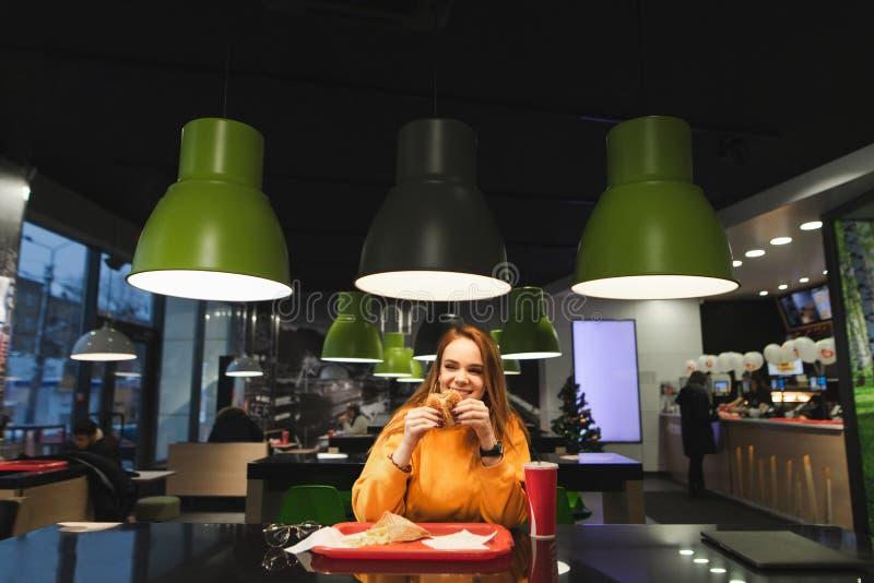 Ευτυχές ελκυστικό κορίτσι σε έναν καφέ στον πίνακα με έναν δίσκο του νόστιμου γρήγορου φαγητού που τρώει και που τρώει και που χα στοκ φωτογραφίες με δικαίωμα ελεύθερης χρήσης