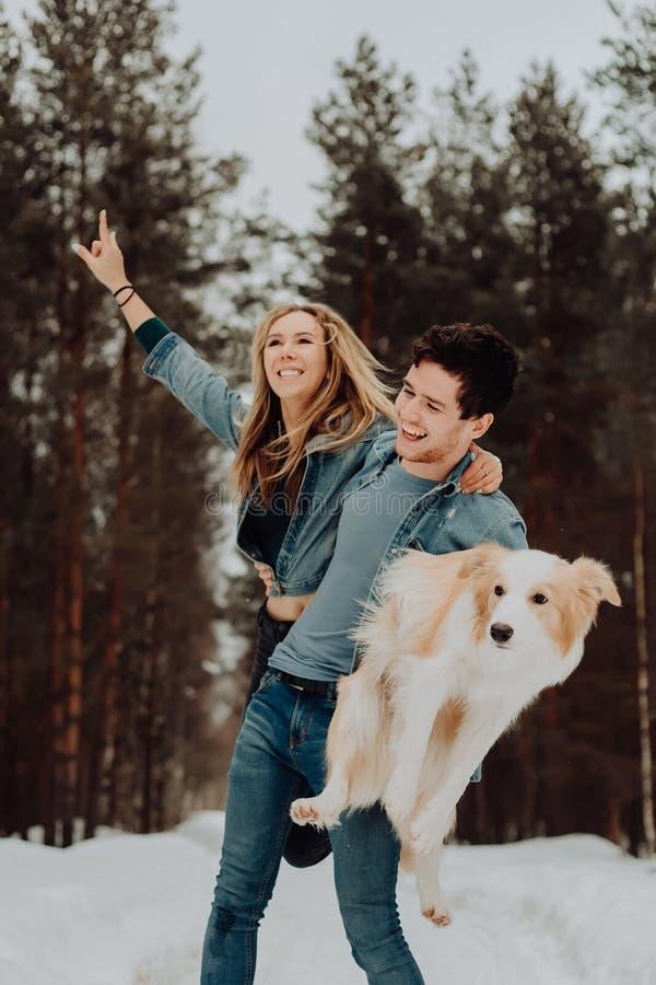 Ευτυχές εύθυμο χαμογελώντας άτομο με το κορίτσι και το σκυλί σε ετοιμότητα του ζεύγος των νέων στα κοστούμια τζιν στο χιονώδες δά στοκ φωτογραφία