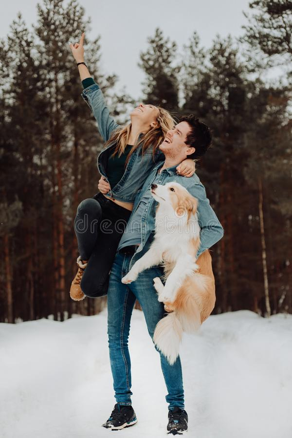 Ευτυχές εύθυμο χαμογελώντας άτομο με το κορίτσι και το σκυλί σε ετοιμότητα του ζεύγος των νέων στα κοστούμια τζιν στο χιονώδες δά στοκ εικόνα