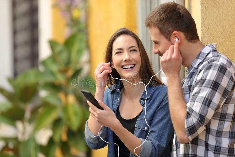Ευτυχές ζεύγος που μοιράζεται τη μουσική σε μια ζωηρόχρωμη οδό στοκ φωτογραφία