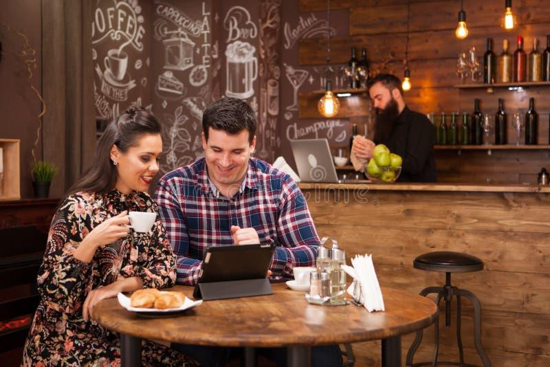 Ευτυχές ζεύγος που χρησιμοποιεί την ψηφιακή ταμπλέτα ενώ έχοντας τον καφέ στο εστιατόριο στοκ εικόνα