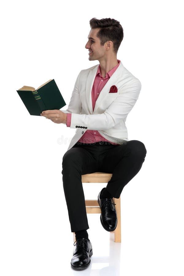 Ευτυχές κομψό άτομο που κάθεται και που παρουσιάζει βιβλίο του στην πλευρά στοκ φωτογραφία με δικαίωμα ελεύθερης χρήσης