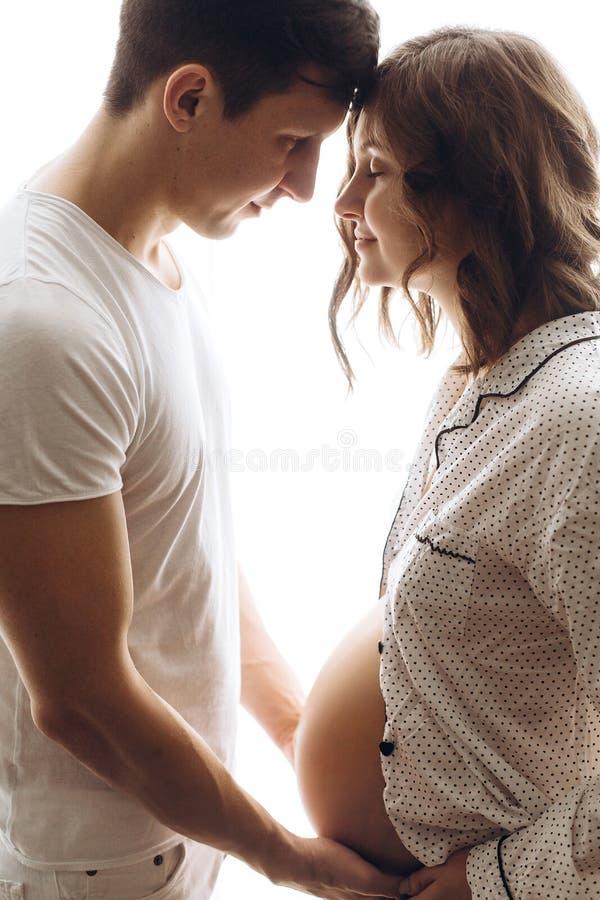 Ευτυχές νέο έγκυο ζεύγος στις άσπρες πυτζάμες που κρατά την πρόσκρουση κοιλιών στο φως πρωινού Μοντέρνοι έγκυοι οικογένεια, mom κ στοκ φωτογραφία με δικαίωμα ελεύθερης χρήσης