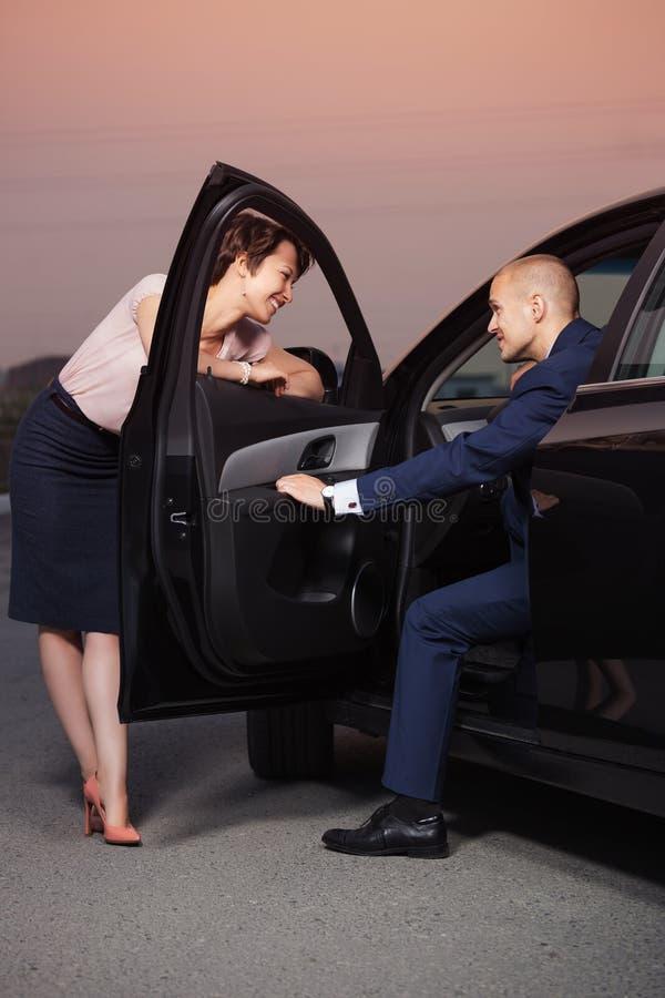 Ευτυχές νέο ζεύγος που μιλά μέσω της πόρτας αυτοκινήτων στοκ φωτογραφία με δικαίωμα ελεύθερης χρήσης