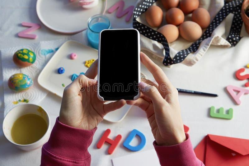 Ευτυχές να προετοιμαστεί Πάσχας Θηλυκά χέρια που κρατούν το κινητό τηλέφωνο και που κάνουν τη φωτογραφία των ζωηρόχρωμων αυγών Πά στοκ φωτογραφία με δικαίωμα ελεύθερης χρήσης
