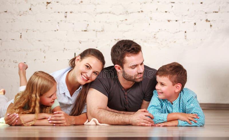 Ευτυχές ονειροπόλο νέο ζεύγος των γονέων με δύο παιδιά τους στο σπίτι από κοινού στοκ φωτογραφία με δικαίωμα ελεύθερης χρήσης