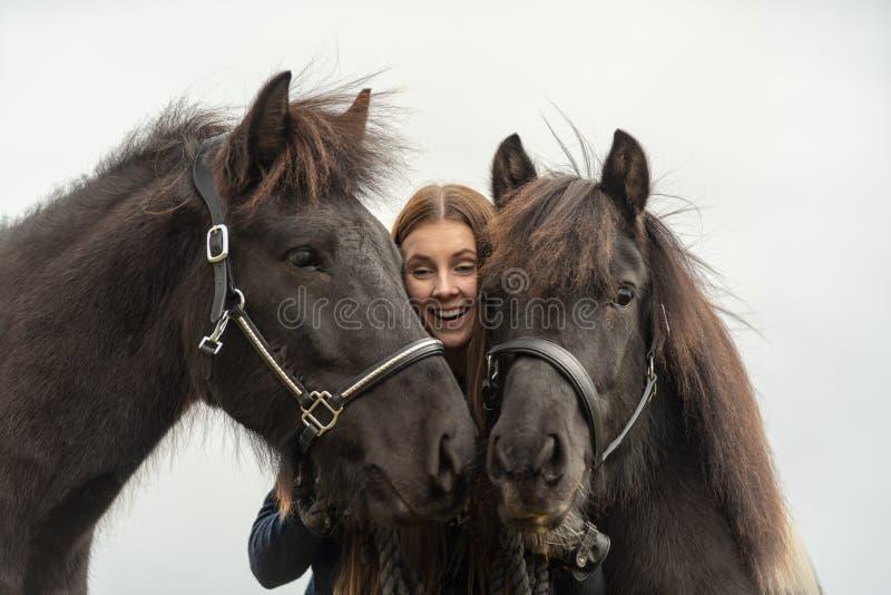 Ευτυχές σουηδικό κορίτσι που αγκαλιάζει και που κρατά δύο σκοτεινά ισλανδικά άλογά της στοκ φωτογραφία με δικαίωμα ελεύθερης χρήσης