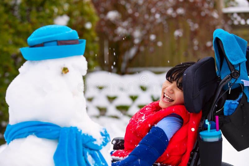 Ευτυχές χαμογελώντας με ειδικές ανάγκες αγόρι στην αναπηρική καρέκλα που χτίζει έναν χιονάνθρωπο στοκ εικόνες με δικαίωμα ελεύθερης χρήσης