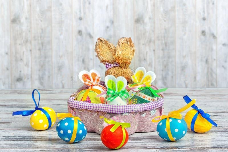Ευτυχές Πάσχα! Υπόβαθρο με τα ζωηρόχρωμα αυγά στο καλάθι και στον πίνακα Έκπληξη από τους λαγούς στοκ εικόνα