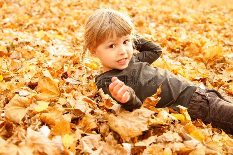 Ευτυχές παιχνίδι παιδιών στα φύλλα φθινοπώρου στη φύση στοκ εικόνα