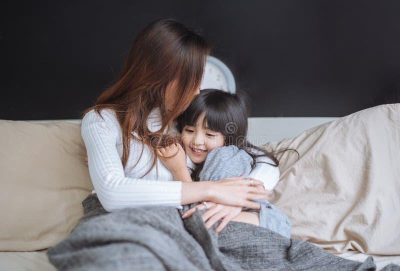 Ευτυχές mom και το κορίτσι κορών της που παίζουν και που αγκαλιάζουν στην κρεβατοκάμαρα στοκ φωτογραφίες