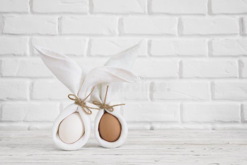 Ευτυχής έννοια υποβάθρου Πάσχας Άσπρο ίδιο λαγουδάκι ή κουνέλι υφασμάτων μινιμαλισμού για το δώρο ή παρόν στον άσπρο τουβλότοιχο στοκ εικόνες