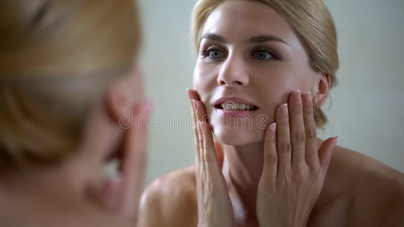 Ευτυχής γυναίκα σχετικά με το πρόσωπο, καλή επίδραση του αντι λοσιόν γήρανσης, skincare καθημερινά στοκ εικόνα με δικαίωμα ελεύθερης χρήσης
