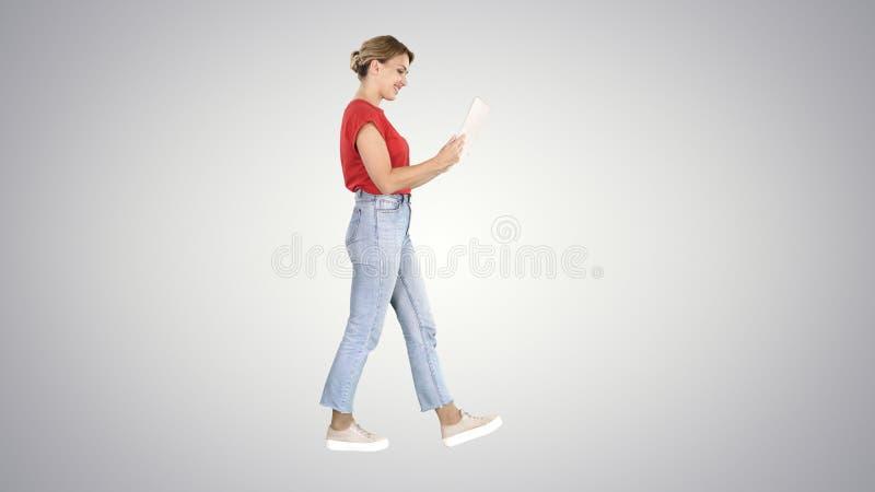 Ευτυχής γυναίκα που περπατά με την ταμπλέτα στο υπόβαθρο κλίσης στοκ φωτογραφία με δικαίωμα ελεύθερης χρήσης