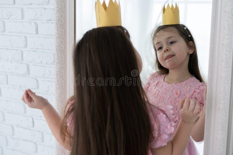 Ευτυχής λίγη πριγκήπισσα κοιτάζει μέσα στον καθρέφτη στοκ εικόνες