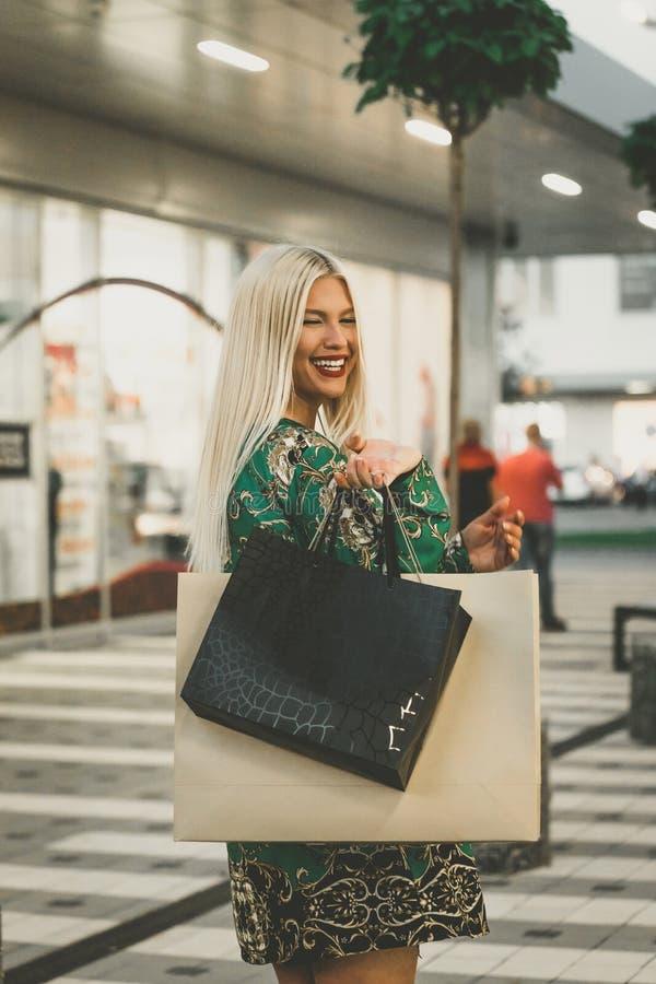 Ευτυχής νέα γυναίκα με τις τσάντες αγορών που απολαμβάνει στις αγορές στοκ εικόνες