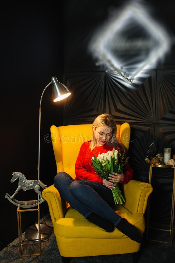 Ευτυχής νέα συνεδρίαση γυναικών στην κίτρινη πολυθρόνα με την ανθοδέσμη των άσπρων λουλουδιών όμορφες τουλίπες 8ος του Μαρτίου στοκ εικόνες
