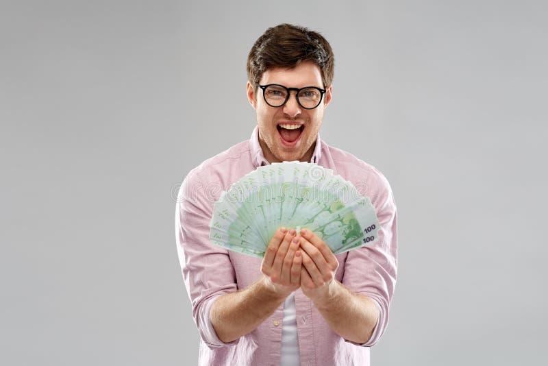 Ευτυχής νεαρός άνδρας στα γυαλιά με τον ανεμιστήρα των ευρο- χρημάτων στοκ εικόνα